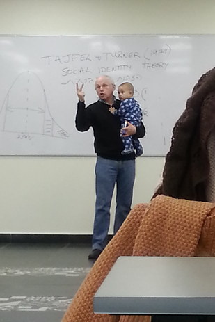 Look at him, teaching away, baby in hand. (image via buzzfeed.com)